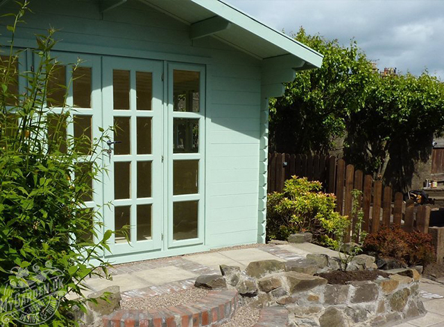 Close up image of a Teal colour garden shed with glass pane windows