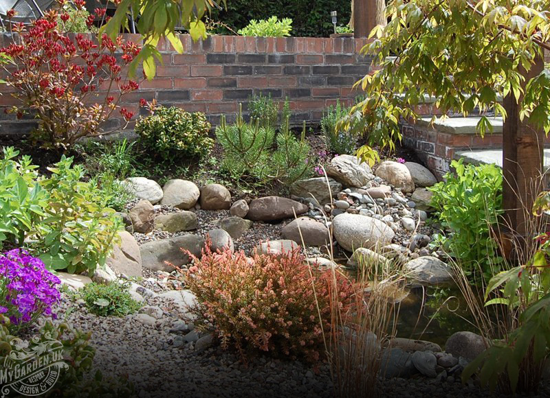 Garden Landscaping rockery area with plants and small pond